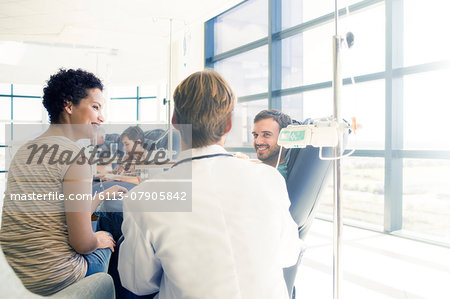 Doctor talking to patient receiving medical treatment in hospital ward Stock Photo - Premium Royalty-Free, Image code: 6113-07905842