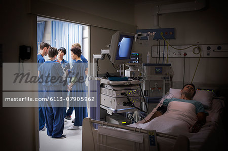 Patient lying in bed in intensive care unit, team of doctors discussing in background Stock Photo - Premium Royalty-Free, Image code: 6113-07905962