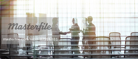 Business people standing in conference room shaking hands Stock Photo - Premium Royalty-Free, Image code: 6113-07906001