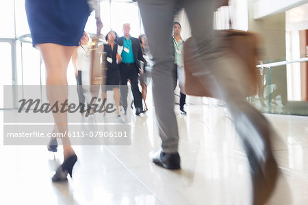 Legs of businesswoman and businessman carrying hand luggage walking through lobby of conference center Stock Photo - Premium Royalty-Free, Image code: 6113-07906101