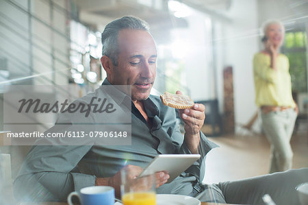 Older man using digital tablet at breakfast table Stock Photo - Premium Royalty-Free, Image code: 6113-07906148