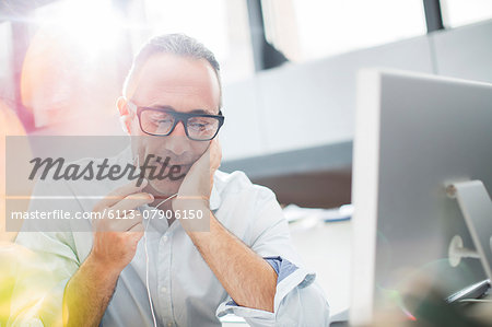 Businessman listening to earbuds at office desk Stock Photo - Premium Royalty-Free, Image code: 6113-07906150