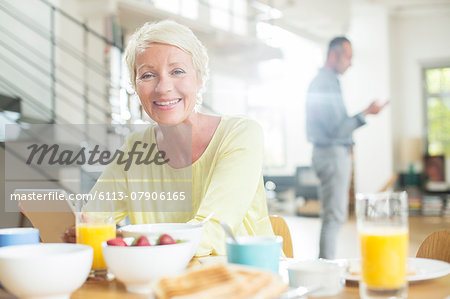 Older woman using digital tablet at breakfast table Stock Photo - Premium Royalty-Free, Image code: 6113-07906165