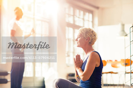 Older woman meditating on floor Stock Photo - Premium Royalty-Free, Image code: 6113-07906211