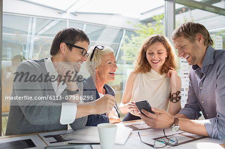 Business people using cell phone in office meeting Stock Photo - Premium Royalty-Free, Image code: 6113-07906295
