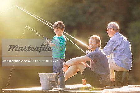 Boy, father and grandfather fishing on wooden dock