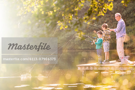 Grandfather and grandsons fishing at lake Stock Photo - Premium Royalty-Free, Image code: 6113-07906373