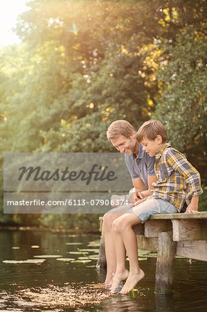 Father and son dangling feet in lake Stock Photo - Premium Royalty-Free, Image code: 6113-07906374