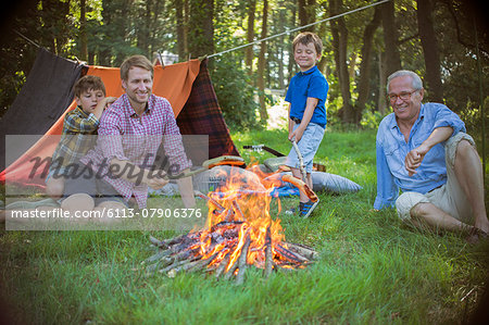 Boy, father and grandfather relaxing near campfire Stock Photo - Premium Royalty-Free, Image code: 6113-07906376