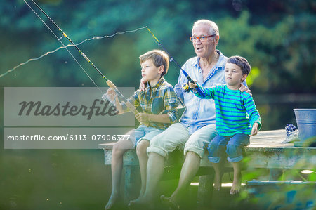 Grandfather and grandsons fishing in lake Stock Photo - Premium Royalty-Free, Image code: 6113-07906377
