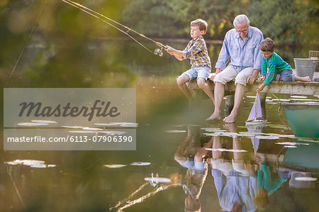 Grandfather and grandsons fishing and playing with toy sailboat at lake Stock Photo - Premium Royalty-Free, Image code: 6113-07906390