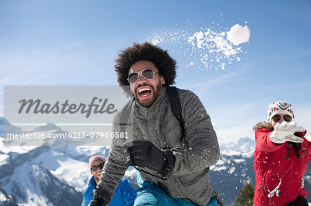 Friends enjoying snowball fight Stock Photo - Premium Royalty-Free, Image code: 6113-07906581
