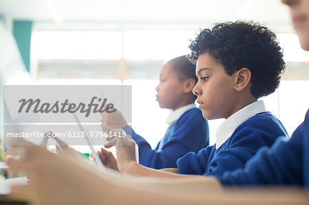 Schoolboys and schoolgirls sitting in classroom using tablet pc's Stock Photo - Premium Royalty-Free, Image code: 6113-07961419