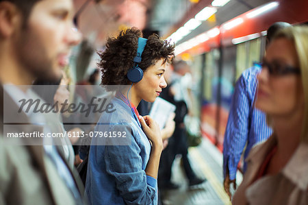 Woman listening to headphones in train station Stock Photo - Premium Royalty-Free, Image code: 6113-07961592