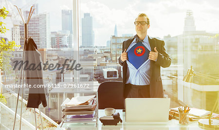 Businessman revealing superhero costume under suit Stock Photo - Premium Royalty-Free, Image code: 6113-07961672