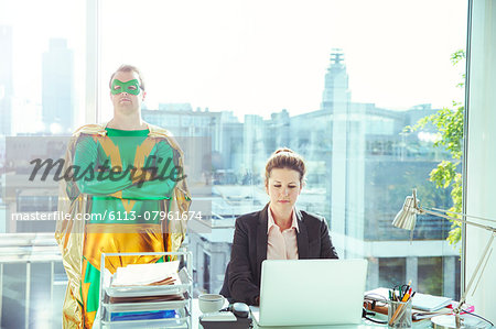 Superhero standing near businesswoman working in office Stock Photo - Premium Royalty-Free, Image code: 6113-07961674