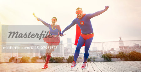 Superheroes holding hands running on city rooftop Stock Photo - Premium Royalty-Free, Image code: 6113-07961678
