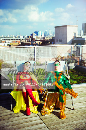 Superhero couple sitting on city rooftop Stock Photo - Premium Royalty-Free, Image code: 6113-07961681