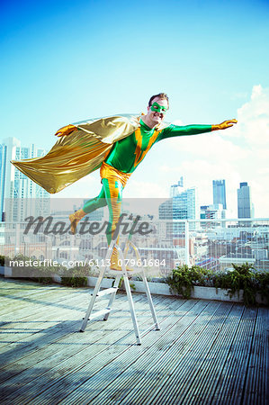 Superhero posing on stepladder on city rooftop Stock Photo - Premium Royalty-Free, Image code: 6113-07961684