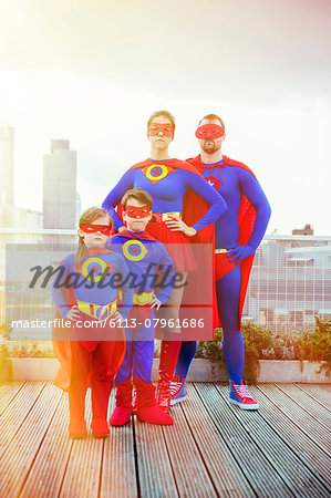 Superhero family standing on city rooftop Stock Photo - Premium Royalty-Free, Image code: 6113-07961686
