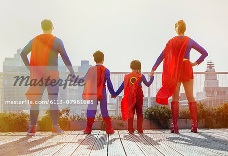 Superhero family standing on city rooftop Stock Photo - Premium Royalty-Free, Image code: 6113-07961688