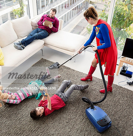Superhero vacuuming around family in living room Stock Photo - Premium Royalty-Free, Image code: 6113-07961690