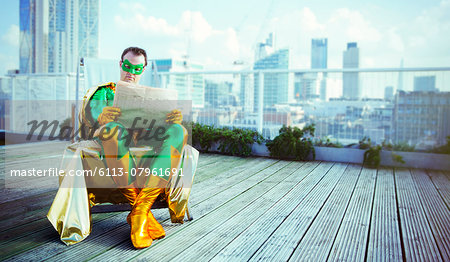 Superhero reading newspaper on city rooftop Stock Photo - Premium Royalty-Free, Image code: 6113-07961691