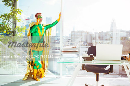 Superhero talking on cell phone in office Stock Photo - Premium Royalty-Free, Image code: 6113-07961693