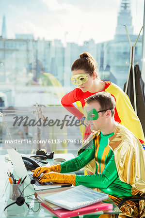 Superheroes working on laptop in office Stock Photo - Premium Royalty-Free, Image code: 6113-07961695