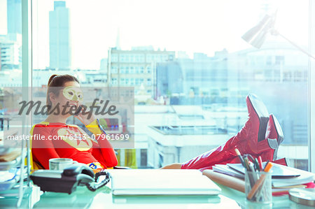 Superhero talking on cell phone at office desk Stock Photo - Premium Royalty-Free, Image code: 6113-07961699