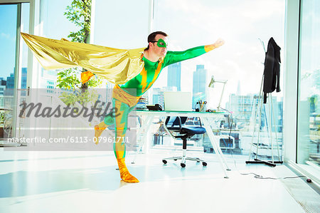 Superhero flying in office Stock Photo - Premium Royalty-Free, Image code: 6113-07961711