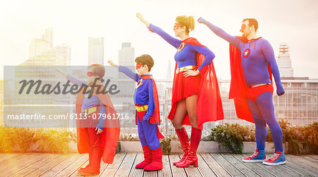 Superhero family standing with arms outstretched on city rooftop Stock Photo - Premium Royalty-Free, Image code: 6113-07961716