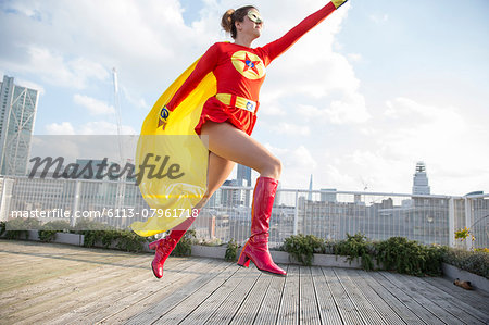 Superhero jumping on city rooftop Stock Photo - Premium Royalty-Free, Image code: 6113-07961718