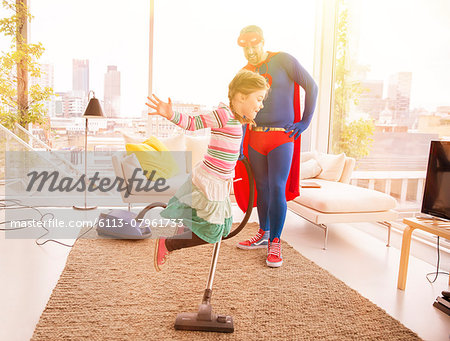 Superhero father vacuuming while daughter jumps in living room Stock Photo - Premium Royalty-Free, Image code: 6113-07961733