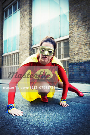 Superhero crouching on city street Stock Photo - Premium Royalty-Free, Image code: 6113-07961736