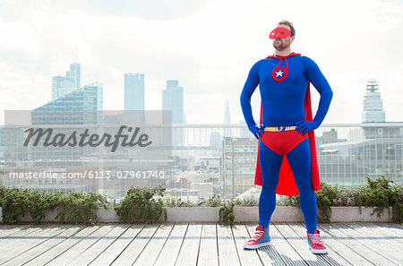 Superhero standing with hands on hips on city rooftop Stock Photo - Premium Royalty-Free, Image code: 6113-07961740