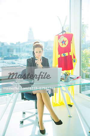 Businesswoman working at office desk with superhero costume behind her Stock Photo - Premium Royalty-Free, Image code: 6113-07961741
