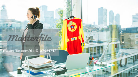 Businesswoman talking on cell phone with superhero costume behind her Stock Photo - Premium Royalty-Free, Image code: 6113-07961742