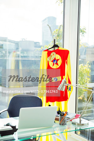 Superhero costume hanging in business office Stock Photo - Premium Royalty-Free, Image code: 6113-07961743