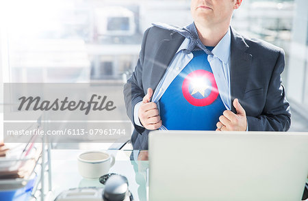 Businessman opening shirt to reveal superhero costume Stock Photo - Premium Royalty-Free, Image code: 6113-07961744