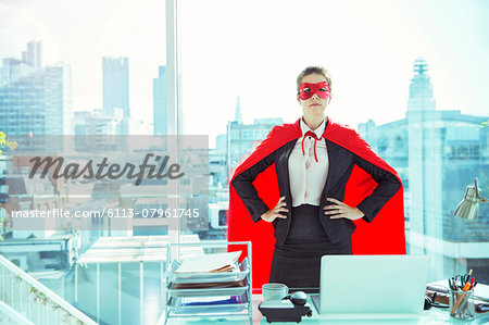 Businesswoman wearing cape and mask in office Stock Photo - Premium Royalty-Free, Image code: 6113-07961745