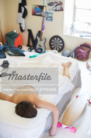 Teenage boy sleeping in bed in his messy room Stock Photo - Premium Royalty-Free, Image code: 6113-07991958