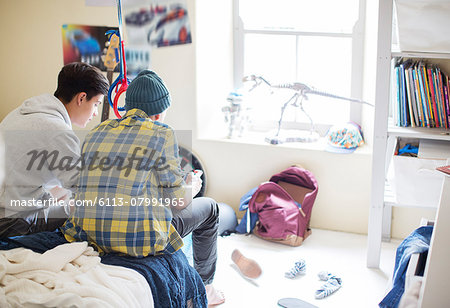 Two teenage boys sitting on bed in messy room Stock Photo - Premium Royalty-Free, Image code: 6113-07991965