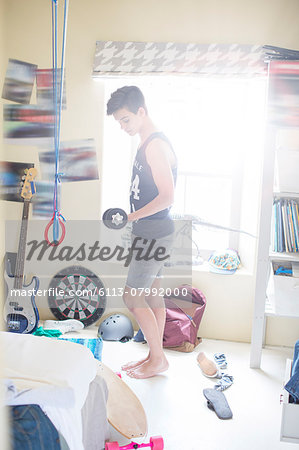 Teenage boy exercising with dumb bell in his room Stock Photo - Premium Royalty-Free, Image code: 6113-07992000