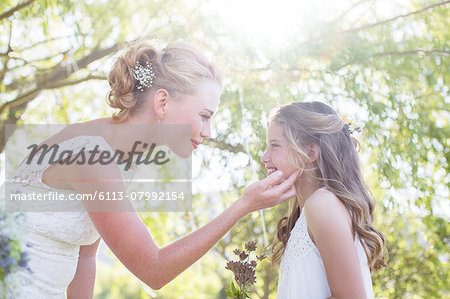 Bride and bridesmaid facing each other in domestic garden during wedding reception Stock Photo - Premium Royalty-Free, Image code: 6113-07992154