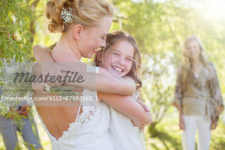 Bride embracing bridesmaid at wedding reception in domestic garden Stock Photo - Premium Royalty-Free, Image code: 6113-07992165