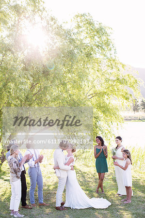 Young couple embracing and kissing during wedding ceremony in domestic garden Stock Photo - Premium Royalty-Free, Image code: 6113-07992183