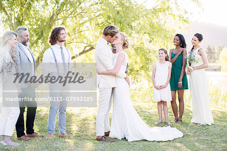 Young couple embracing and kissing during wedding ceremony in domestic garden Stock Photo - Premium Royalty-Free, Image code: 6113-07992185