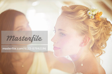 Portrait of bride with bridesmaid in background in domestic room Stock Photo - Premium Royalty-Free, Image code: 6113-07992196