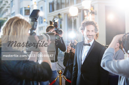 Smiling celebrity in tuxedo being photographed by paparazzi at red carpet event Stock Photo - Premium Royalty-Free, Image code: 6113-08088147